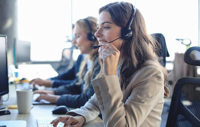 A customer support representative takes a call. Courtesy Adobe Stock.