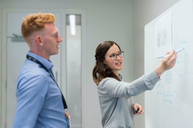 female employee writing on whiteboard with male employee conference room