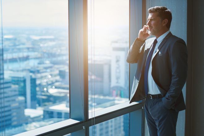 executive looks out window of highrise while talking on smartphone