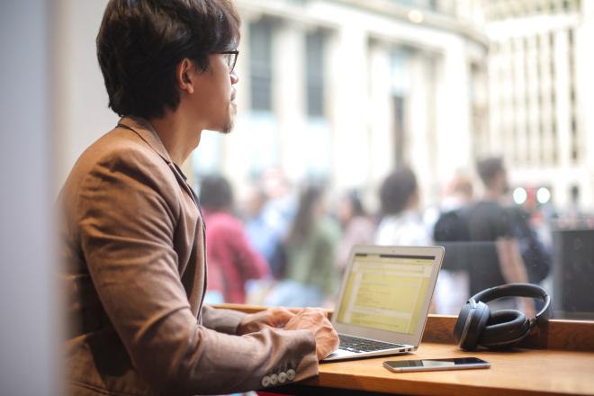 man working coffee shop laptop computer smartphone headphones