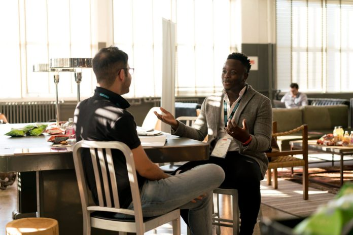 A picture of two men talking at a table, the IBM PartnerWorld program offers channel partners globally the chance to collaborate and service clients with IBM technologies.